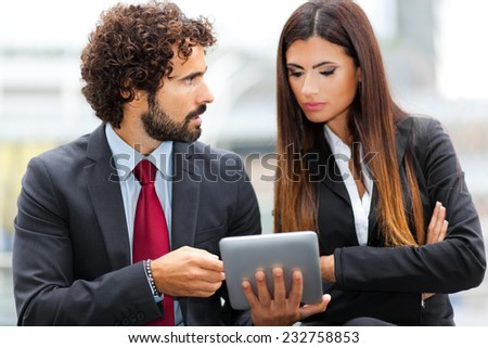 Business people using a digital tablet - stock photo