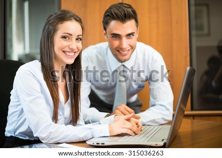 Business people using a laptop computer in their office - stock photo