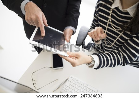 Business people using an electronic tablet - stock photo