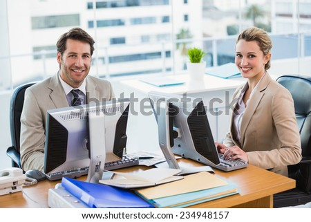 Business people using computer while looking at camera in office - stock photo