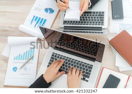 Business people using laptop  and Financial charts  at meeting office - stock photo