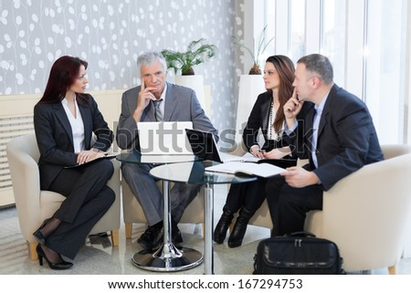 Business people using laptop and talking about a current problems - stock photo