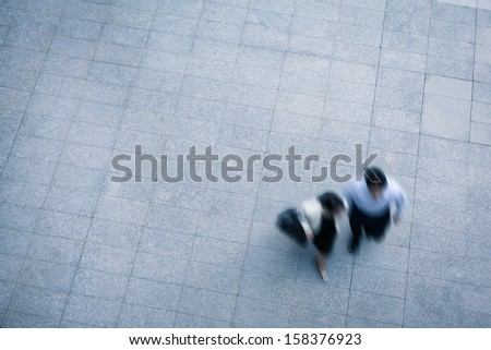 Business people walking and talking in the street, high angle view - stock photo