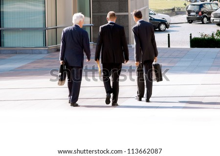 Business people walking down the street with briefcases and folders, chatting. - stock photo