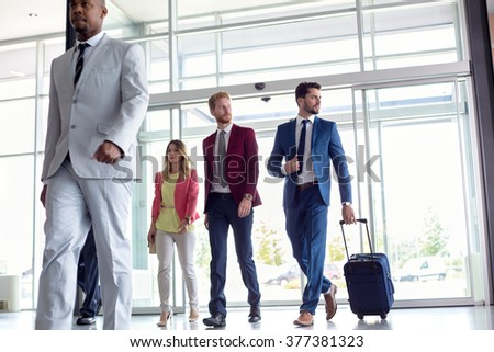 Business people walking in airport - stock photo