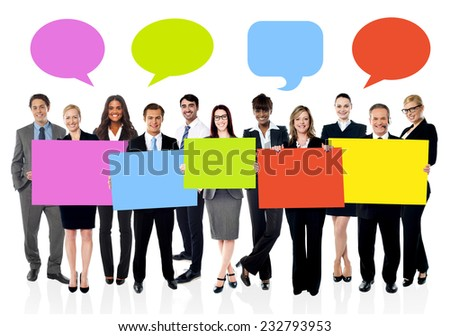Business people with colorful board and speech bubbles above - stock photo