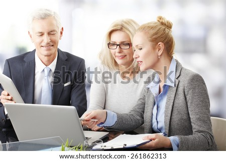 Business people with laptop and digital tablet sitting at desk and working on presentation. Teamwork.  - stock photo