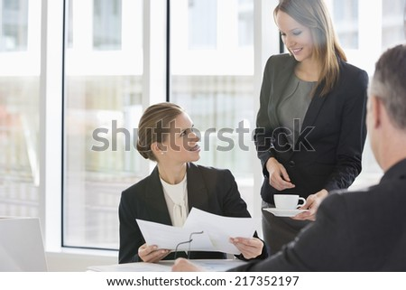 Business people with paperwork during coffee break - stock photo