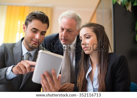 Business people working on a tablet - stock photo