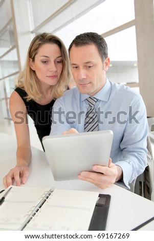 Business people working on electronic tablet - stock photo