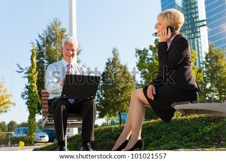 Business people working outdoors - he is working with laptop, she is calling someone - stock photo