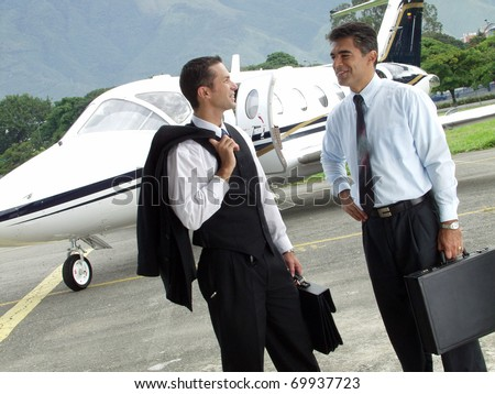Business people working outsider on private jet background. - stock photo