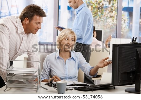 Business people working together in office, using persnal organizer and desktop computer. - stock photo