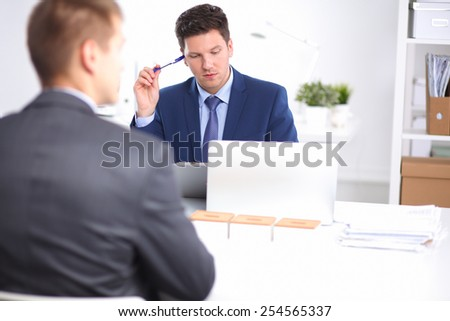 Business people working with laptop in an office, sitting ta the desk. - stock photo