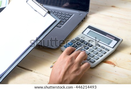 Business,Person Calculating Budget With Calculator At Desk - stock photo