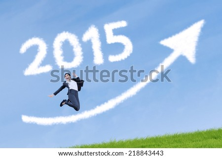 Business person celebrate her success on meadow with upward arrow and number 2015 - stock photo