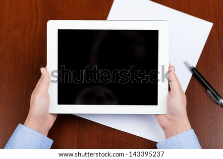 Business person holding a tablet with an empty screen over a desk with a sheet of paper and a pen - stock photo