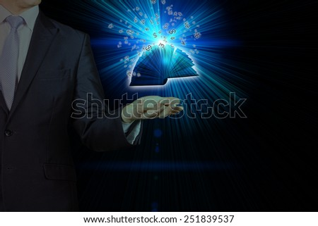 business person holding shining book with the symbols of world currencies. Opened magic book with magic light. - stock photo