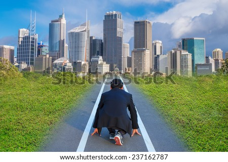 Business person in ready position on track for running and chasing his aim - stock photo