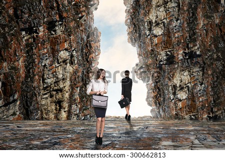 Business person looking at the end of the cave - stock photo