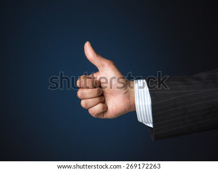 Business person showing thumbs up for success and victory - stock photo