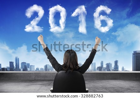 Business person sit on chair looking 2016 cloud shape number. New year concept - stock photo