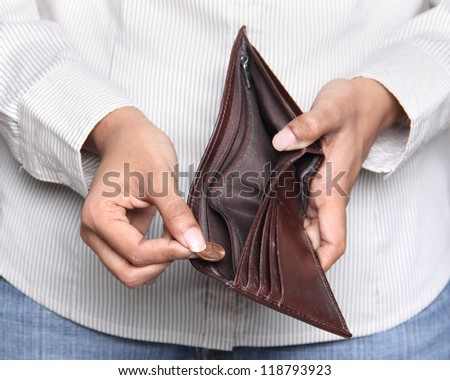 Business person taking a penny from a wallet - stock photo