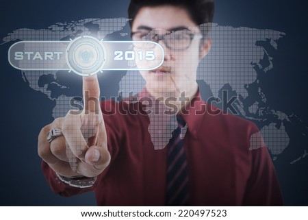 Business person touching a futuristic start button to start his vision - stock photo