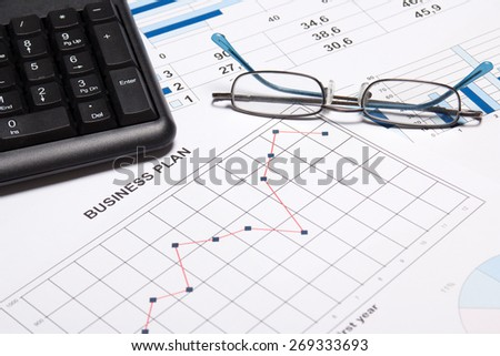 business plan concept - graphs, charts, glasses and computer keyboard - stock photo