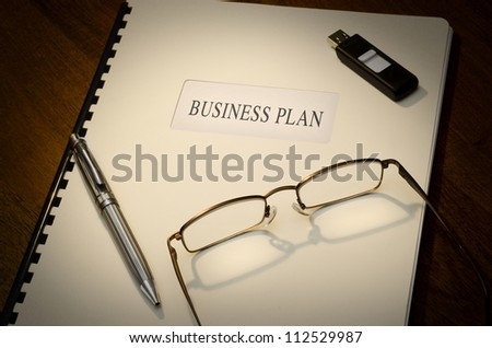 Business Plan on a desk with a pen, a thumb drive and a pair of glasses - stock photo