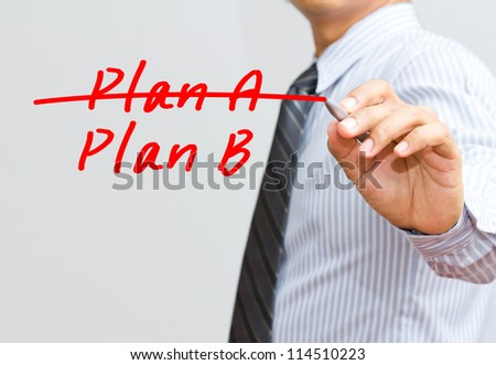 Business plan strategy changing. hand crossing over Plan A, writing Plan B. - stock photo