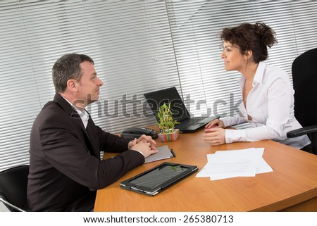 Business plan. Two Confident businesspeople checking documents while two successful businessman sitting in office at the table in the formal wear. - stock photo