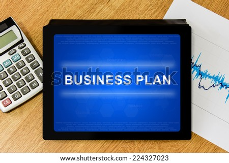 business plan word on digital tablet with calculator and financial graph - stock photo