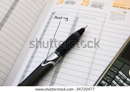 Business planner showing a meeting on friday with a pen and a smart phone - stock photo