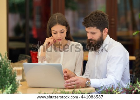 Business pope in a cafe view charts and working on laptop - stock photo