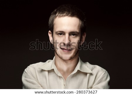 Business portrait of handsome man on a dark background - stock photo