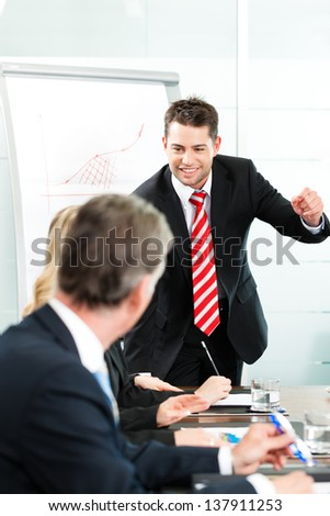 Business - presentation within a team, a colleague is standing on the flipchart	 - stock photo