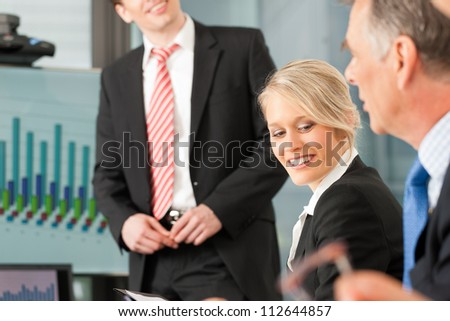 Business - presentation within a team, a male, colleague is standing on the flipchart - stock photo