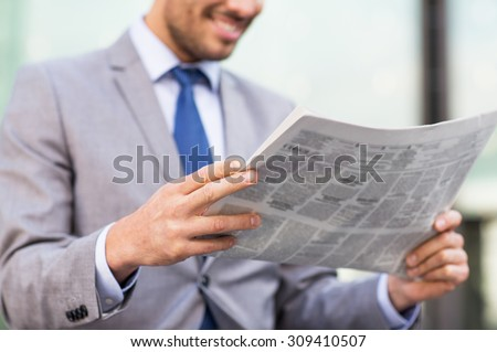 business, press, news and people and concept - close up of young smiling businessman reading newspaper over office building - stock photo