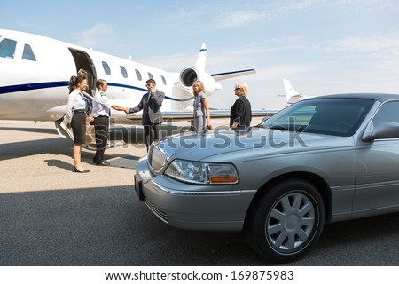 Business professional greeting airhostess and pilot near private jet and limo - stock photo