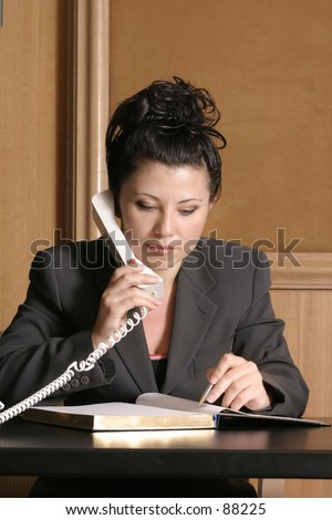 Business professional on phone with schedule/diary - stock photo