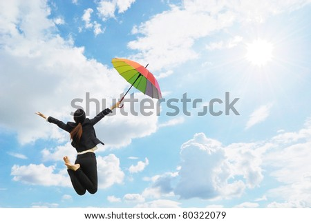 Business rainbow umbrella woman jumping to blue sky - stock photo