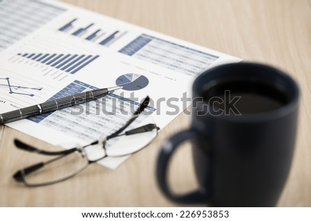 Business report. Cup of coffee and document. - stock photo