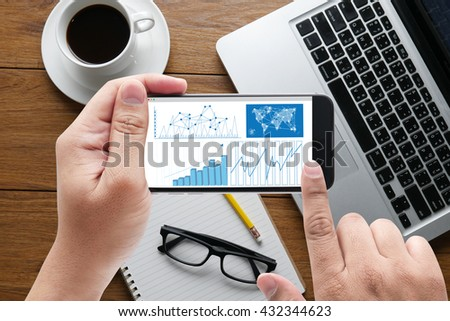 Business Research Data Economy message on hand holding to touch a phone, top view, table computer coffee and book - stock photo