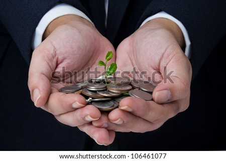 Business's hand holding coins with growing plant - stock photo