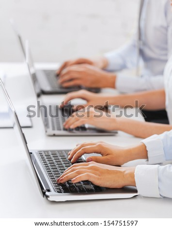 business, school and education concept - group of people working with laptops in office - stock photo