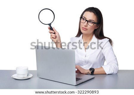 Business search concept. Business woman sitting at desk with laptop holding magnifying glass, isolated over white - stock photo