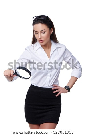 Business search concept. Concentrated business woman looking through magnifying glass at blank copy space, isolated over white - stock photo