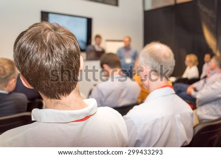 business seminar, people sitting back and the couch at the screen acting the presentation. - stock photo