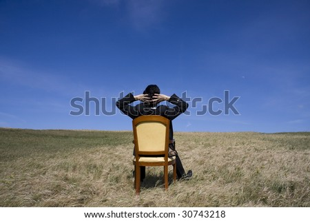 Business sit on a chair looking to the sky - stock photo
